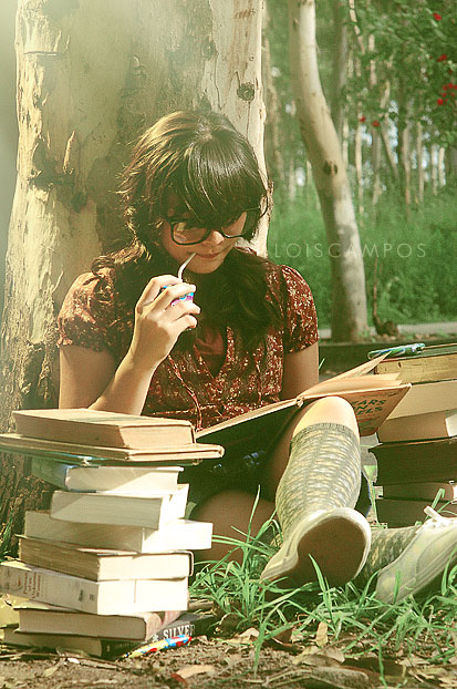 woman reading book in front of tree
