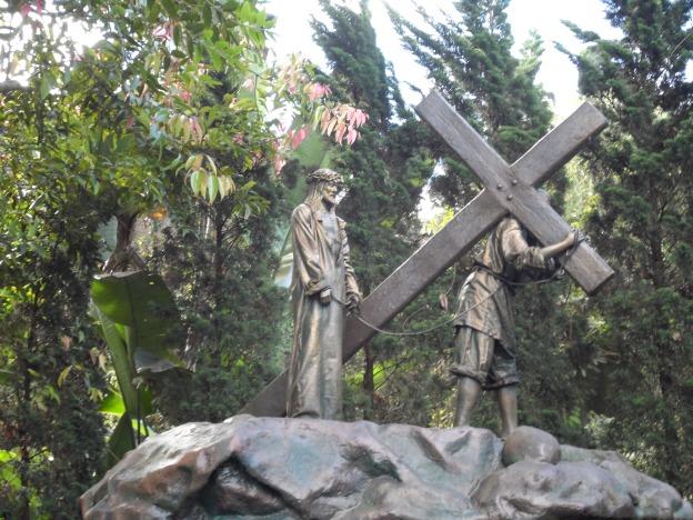 Yesus ditolong oleh Simon dari Kirene.
